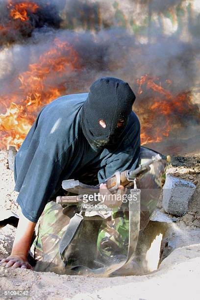 Palestinian Militant Youth Trains How To Use A Weapon As A Fire Burns Behind Him May 11, 2002 In Rafah Refugee Camp, Located In The Gaza Strip....