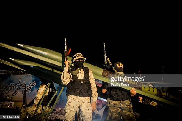 Palestinian militants from the Al-Quds Brigades, the armed wing of the Islamic Jihad movement, sit on a pick-up truck mounted with rockets during a...