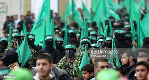 Palestinian militants from the Ezzedine al-Qassam brigade, the armed wing of Hamas, march during a rally to commemorate the 27th anniversary of the...
