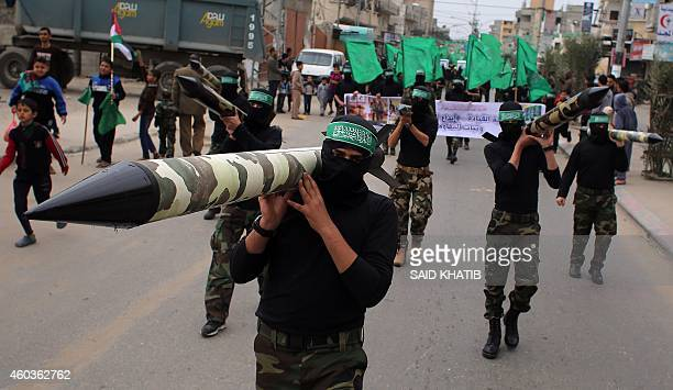 Palestinian militants from the Ezzedine al-Qassam brigade, the armed wing of Hamas, carry mock-rockets as they march during a rally to commemorate...