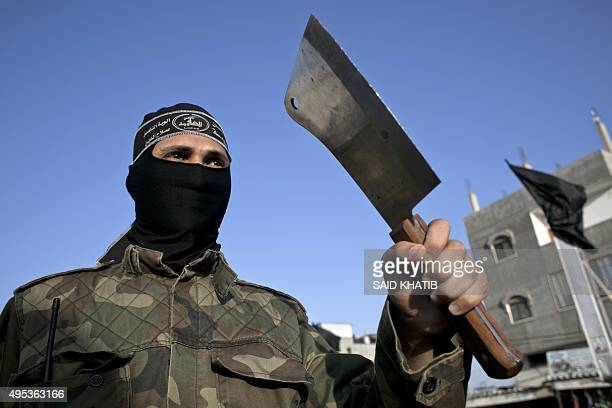 Palestinian militants of alNasser Salah alDeen Brigades the armed wing of the Popular Resistance Committees holds a cleaver during a demonstration to...