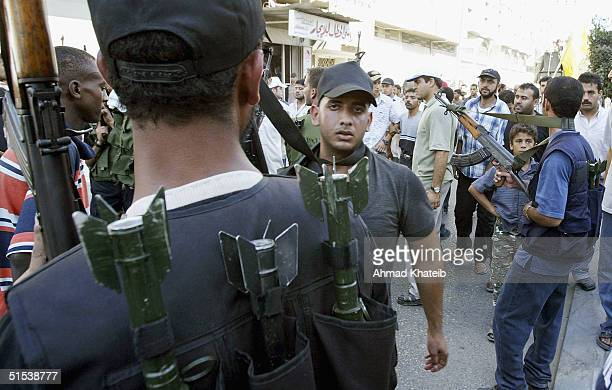 Palestinian militants walk with mourners as they carry the body of Adnan alGhoul a senior member of the Hamas militant group and a master bombmaker...