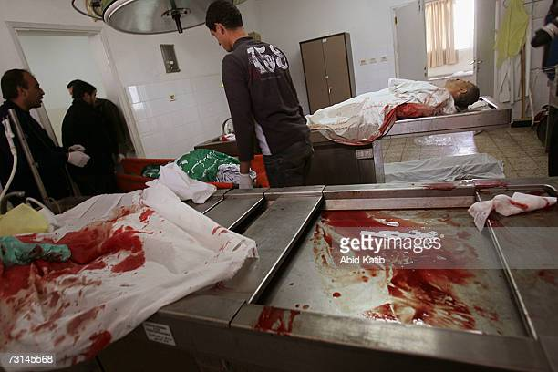 Palestinian morgue workers and relatives prepare the bodies of Hamas member Omar Shorab and Ahmad AlGhandor in The AlShifa hospital on January 29 in...