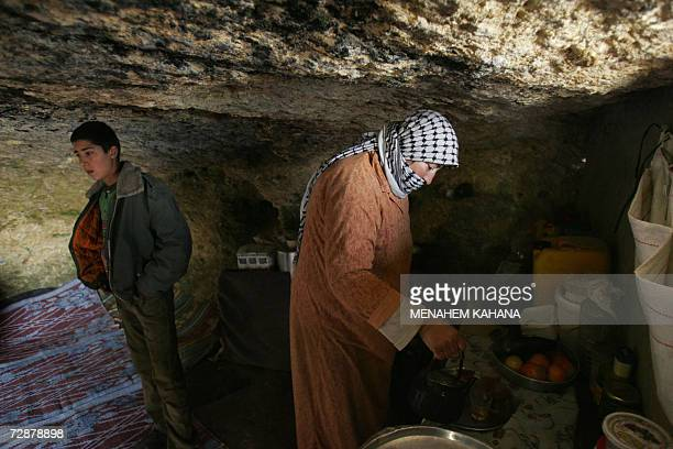 Palestinian mother Bahija Bani Jaber pours out tea as her 14yearold son Yussef looks on in their home a cave where her and her family live during the...