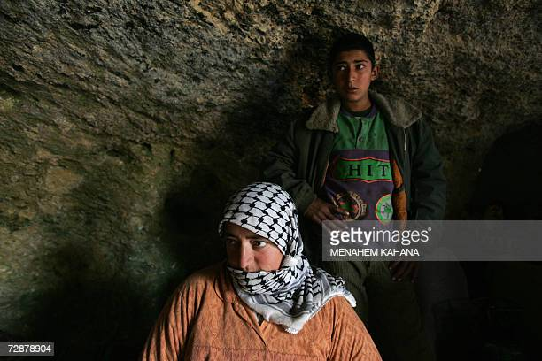 Palestinian mother Bahija Bani Jaber stands with her 14yearold son Yussef in their home a cave where her and her family live during the winter months...