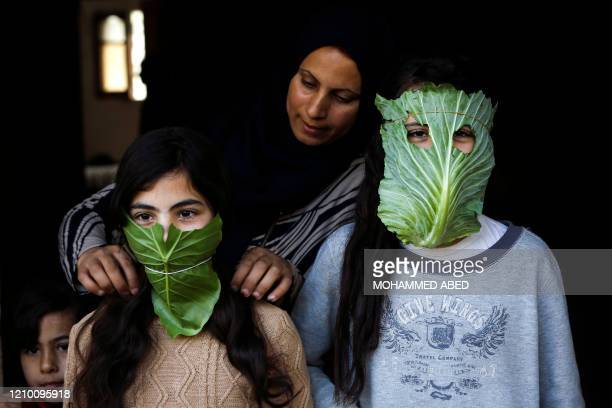 Palestinian mother entertain her children with makeshift masks made of cabbage as she cooks in Beit Lahia in the northern Gaza Strip on April 16,...