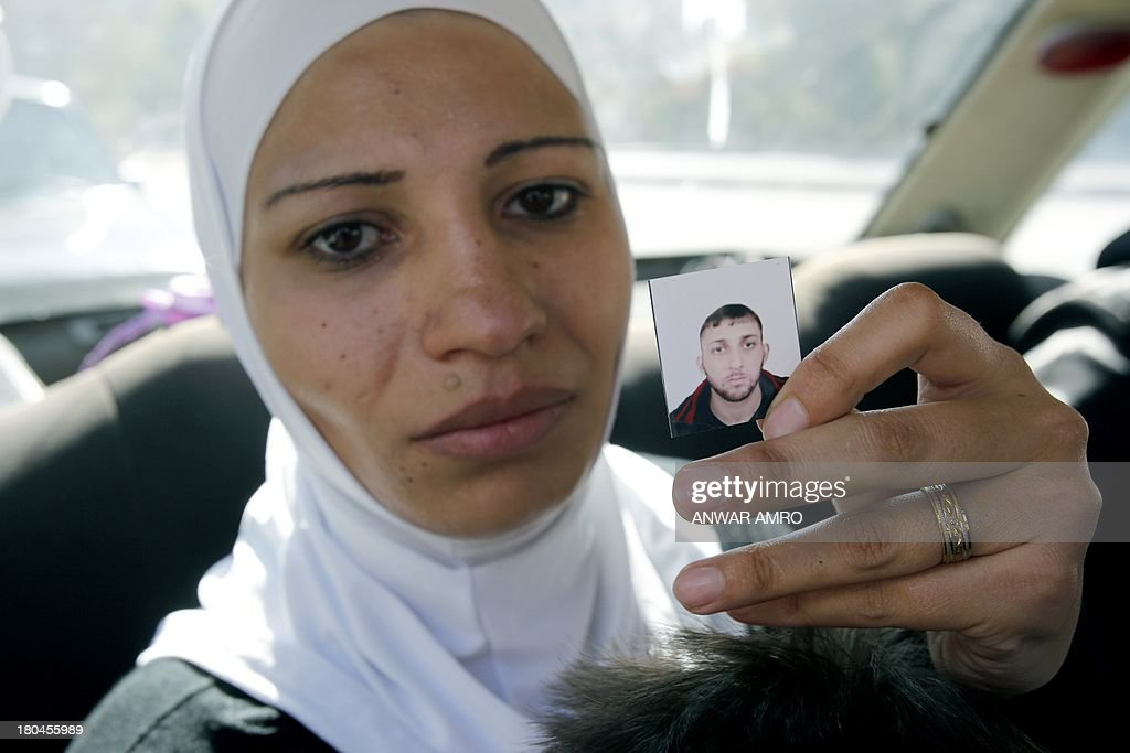 Palestinian mother Hadia al-Fut holds a photograph of her Syrian husband Mohammed, 27, a member of the Popular Front for the Liberation of Palestine General Command (PFLP-GC) who was killed during ...