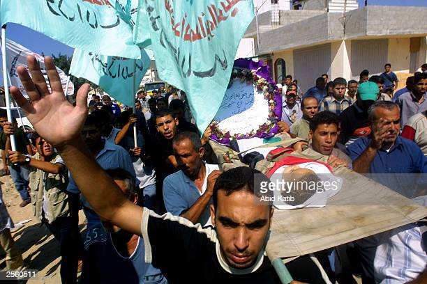 Palestinian mourners and relatives of 18monthold baby Mostafa Badrasawi carry his body during his funeral October 4 2003 at the Khan Younis refugee...