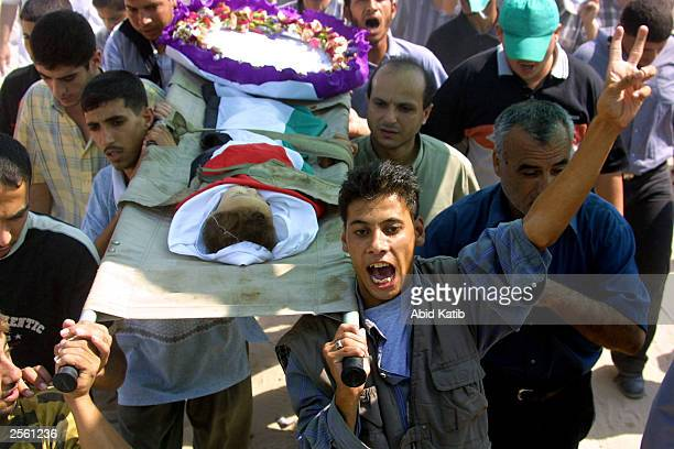 Palestinian mourners and relatives of 18monthold baby Mostafa Badrasawi shout antiIsraeli slogans as they carry his body during his funeral October 4...