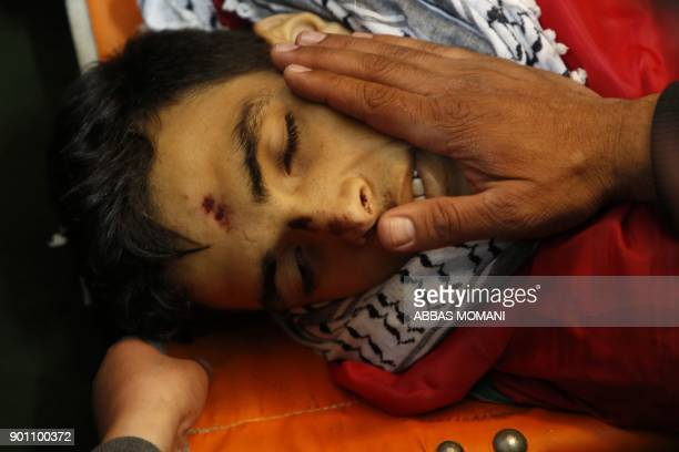 Palestinian mourners caress the face of Musab Firas alTamimi who was shot dead in clashes with the Israeli army a day earlier during his funeral in...