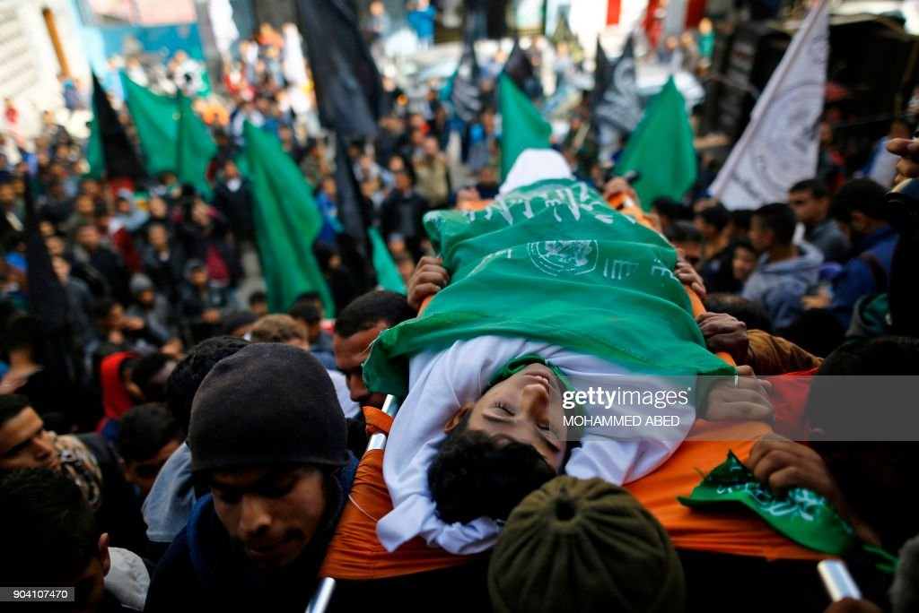Palestinian mourners carry the body of Amir Abu Musaid, 16, during his funeral in the al-Maghazi refugee camp, located in in the centre of the Gaza Strip, after he was shot dead in clashes with the Israeli military along the Gaza border the previous day, on January 12, 2018. /