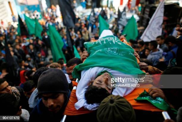 Palestinian mourners carry the body of Amir Abu Musaid during his funeral in the alMaghazi refugee camp located in in the centre of the Gaza Strip...