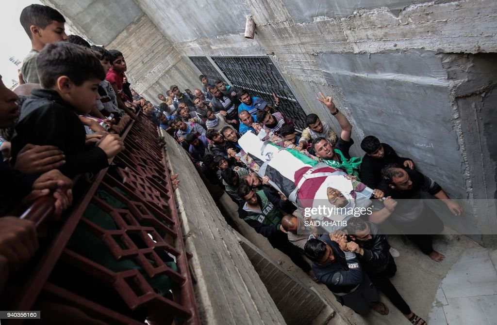 Palestinian mourners carry the body of Ibrahim Abu Shaer, who was killed a day earlier by Israeli forces when clashes erupted as tens of thousands as Gazans marched near the Israeli border with the enclave to mark Land Day, during his funeral in Rafah, in the southern Gaza Strip, on March 31, 2018. Sixteen Palestinians were killed and hundreds more wounded in the conflict's worst single day of violence since the 2014 Gaza war. Israel's military targeted three Hamas sites in the Gaza Strip with tank fire and an air strike after what it said was an attempted shooting attack against soldiers along the border that caused no injuries. Protesters, including women and children, gathered at multiple sites throughout the blockaded territory, which is flanked by Israel along its eastern and northern borders. KHATIB