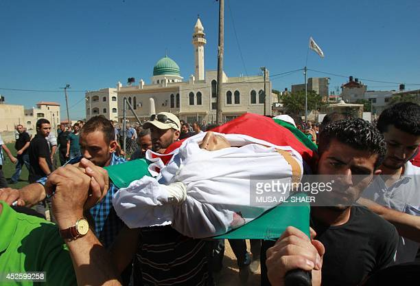 Palestinian mourners carry the body of Mahmud alHamamra who was shot dead by Israeli troops during clashes in the West Bank the previous day during...