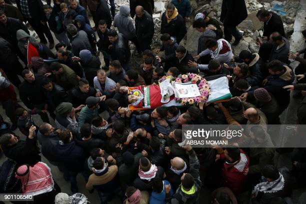 Palestinian mourners carry the body of Musab Firas alTamimi who was shot dead in clashes with the Israeli army a day earlier during his funeral in...
