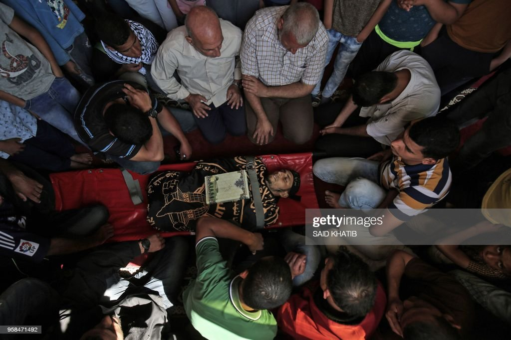 TOPSHOT - Palestinian mourners gather around the body of a man who was killed during a protest at the Israel-Gaza border on May 14, 2018, during his funeral at a mosque in Khan Yunis in the southern Gaza Strip. - Palestinians followed through with their vow to protest massively along the Gaza border with tens of thousands demonstrating and 52 killed by Israeli fire as clashes erupted over the controversial inauguration of the US embassy in Jerusalem.