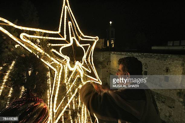 A Palestinian municipal worker fixes the star of Bethlehem on top of the central Christmas tree in Manger Square outside the Church of the Nativity...