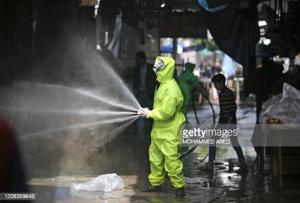 Palestinian municipal workers spray disinfectant as a precaution against the spread of the COVID-19 coronavirus at a market in Gaza City, on March...