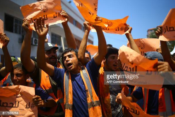 Palestinian municipality workers carry placards reading in Arabic 'No to the siege' during a demonstration against it and in solidarity with AlAqsa...