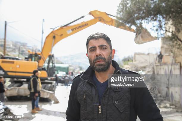Palestinian Murad Hashima speaks during an interview as his relatives demolish a large part of their house to not pay the Jerusalem Municipality any...