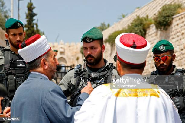 Palestinian Muslim clerics speak with Israeli border guards outside the Lions Gate a main entrance to AlAqsa mosque compound in Jerusalem's Old City...