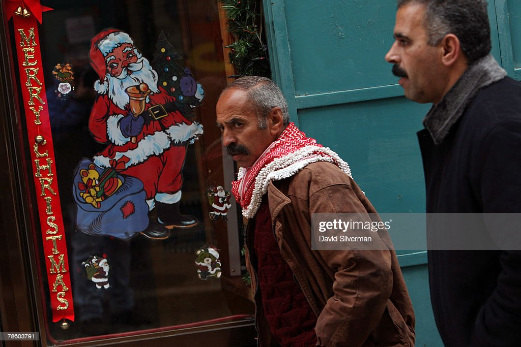Palestinian Muslim men pass a Santa Claus poster in a shop window near Manger Square December 21, 2007 in Bethlehem in the West Bank. The biblical town is celebrating both Christmas and the Muslim Eid al-Adha over the next few days.