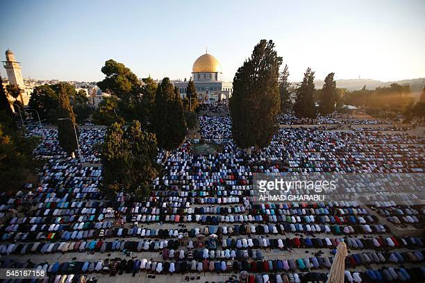 TOPSHOT Palestinian Muslim men perform the morning Eid alFitr prayer near the Dome of Rock at the AlAqsa Mosque compound Islam's third most holy site...