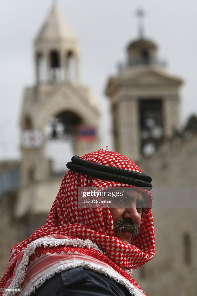 A Palestinian Muslim performs his midday Friday prayers in Manger Square, where the Church of the Nativity is seen in the background, on December 21, 2007 in Bethlehem in the West Bank. The biblical town is celebrating both Christmas and the Muslim Eid al-Adha over the next few days.