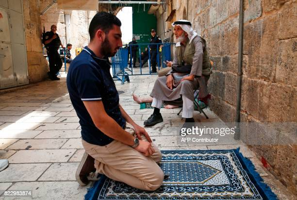 A Palestinian Muslim prays outside the gates of AlAqsa mosque compound in the old city of Jerusalem on July 26 as a tense standoff is underway...