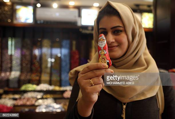 A Palestinian Muslim woman poses for a photo holding a chocolate bearing an image of Santa Claus at a shop in Gaza City on December 22 as Christians...