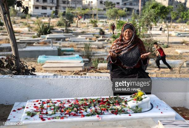 Palestinian Muslim woman prays at the grave of a relative in the main cemetery of Beit Lahia in the northern Gaza Strip on May 13 the first day of...