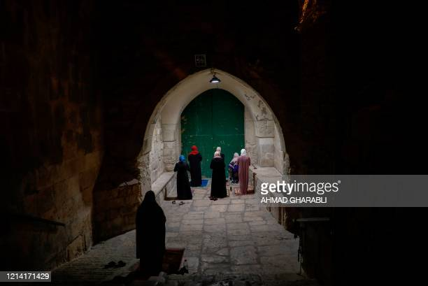 TOPSHOT Palestinian Muslim women worshippers distanced from each other due to the COVID19 coronavirus pandemic pray outside the closed gate of the...