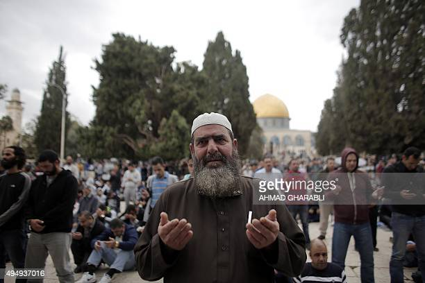Palestinian Muslim worshipers pray outside the Dome of the Rock at the AlAqsa Mosque compound in Jerusalem during Friday prayers on October 30 2015...