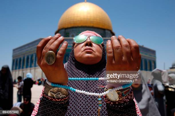 Palestinian Muslim worshipper attends the second Friday prayers of the Muslim holy month of Ramadan in front of the Dome of the Rock at Jerusalem's...