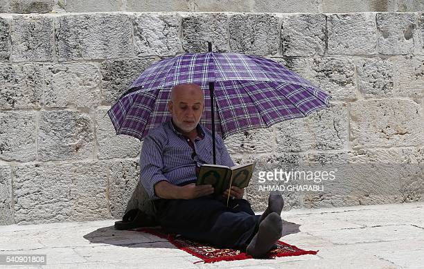 A Palestinian Muslim worshipper holds an umbrella to shield himself from the sun as he reads the Koran during Friday prayer at the alAqsa mosque...
