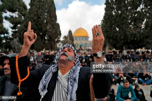 A Palestinian Muslim worshipper prays in front of the Dome of the Rock mosque at the AlAqsa mosque compound in Jerusalem's Old City on December 15...