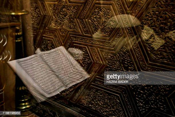Palestinian Muslim worshipper reading the holy Koran is reflected in a mirror during dawn prayer at the Ibrahimi mosque also known as the Tomb of the...