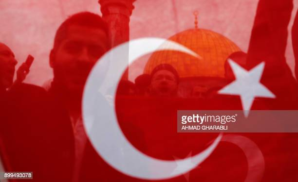 TOPSHOT Palestinian Muslim worshippers are seen through the fabric of a Turkish national flag during a demonstration against the US president's...
