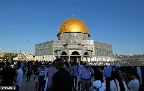 Palestinian Muslim worshippers gather for the morning Eid alFitr prayer near the Dome of Rock at the AlAqsa Mosque compound Islam's third most holy...