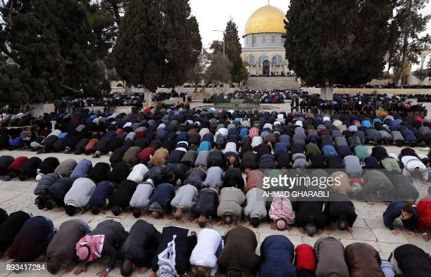 Palestinian Muslim worshippers pray in front of the Dome of the Rock mosque at the AlAqsa mosque compound in Jerusalem's Old City on December 15 2017...
