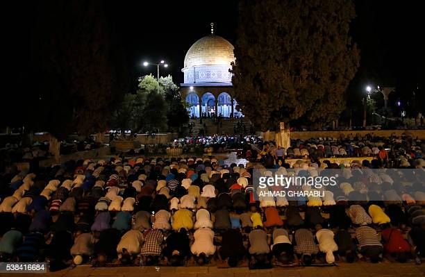 Palestinian Muslim worshippers pray in front of the the Dome of the Rock at the alAqsa Mosque compound in Jerusalem during 'tarawih' prayer marking...