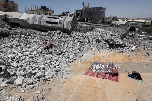 Palestinian Muslim worshippers pray near the rubble of a destroyed mosque in Beit Lahia, in the northern Gaza Strip, on May 27, 2021. - A ceasefire...