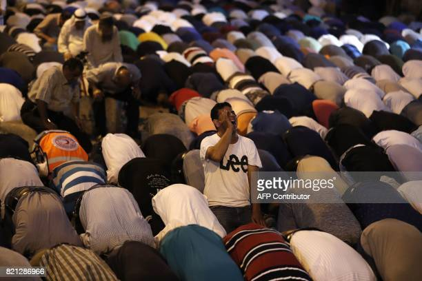 TOPSHOT Palestinian Muslim worshippers pray outside Lions' Gate a main entrance to the AlAqsa mosque compound in Jerusalem's Old City on July 23 in...