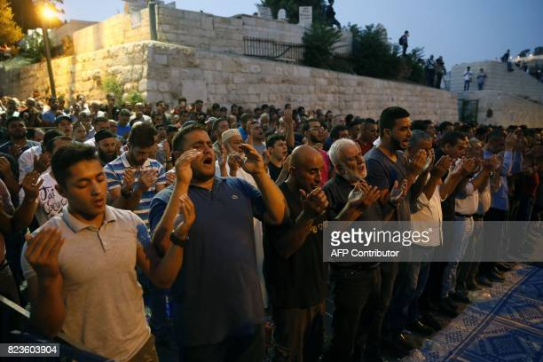 Palestinian Muslim worshippers pray outside Lions' Gate a main entrance to the AlAqsa mosque compound in Jerusalem's Old City on July 27 / AFP PHOTO...