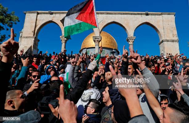 TOPSHOT Palestinian Muslim worshippers shout slogans during Friday prayer in front of the Dome of the Rock mosque at the alAqsa mosque compound in...