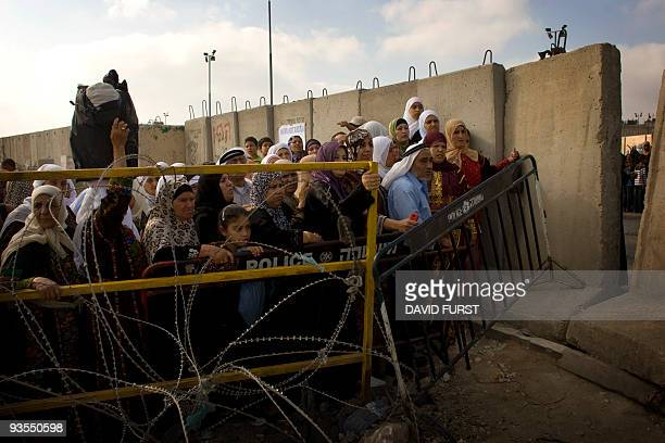 Palestinian Muslim worshippers wait to cross through the West Bank Israeli checkpoint of Qalandia into Jerusalem to attend the second Ramadan Friday...