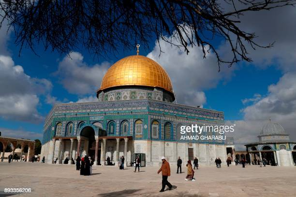 TOPSHOT Palestinian Muslim worshippers walk past the Dome of the Rock mosque at the AlAqsa mosque compound in Jerusalem's Old City on December 15...