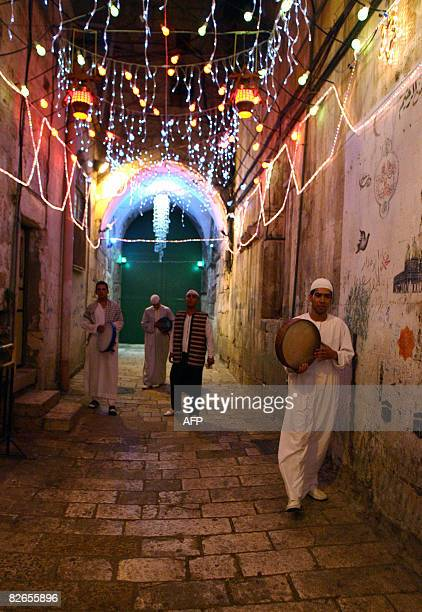 Palestinian Muslim youths play instruments as they call worshippers for Msaharati the traditional Ramadan 3am wakeup call for a final meal before the...