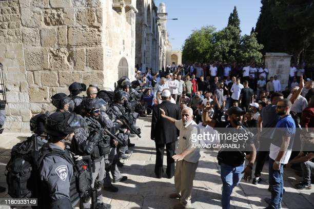 Palestinian Muslims face Israeli security forces as tensions rise inside the AlAqsa Mosque compound in the Old City of Jerusalem on August 11 during...