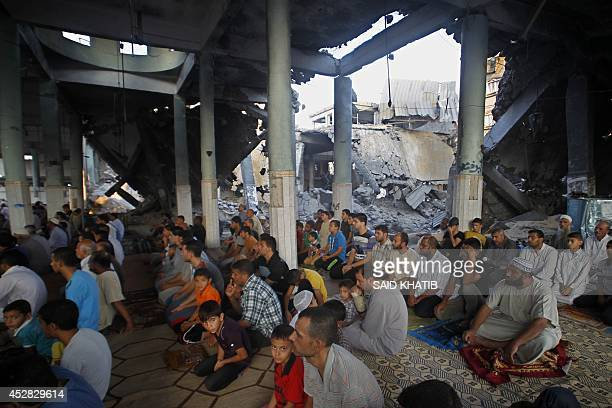 Palestinian Muslims perform a prayer on July 28 on the first day of Eid alFitr at the heavily damaged AlFaruq mosque wich was destroyed a week ago by...